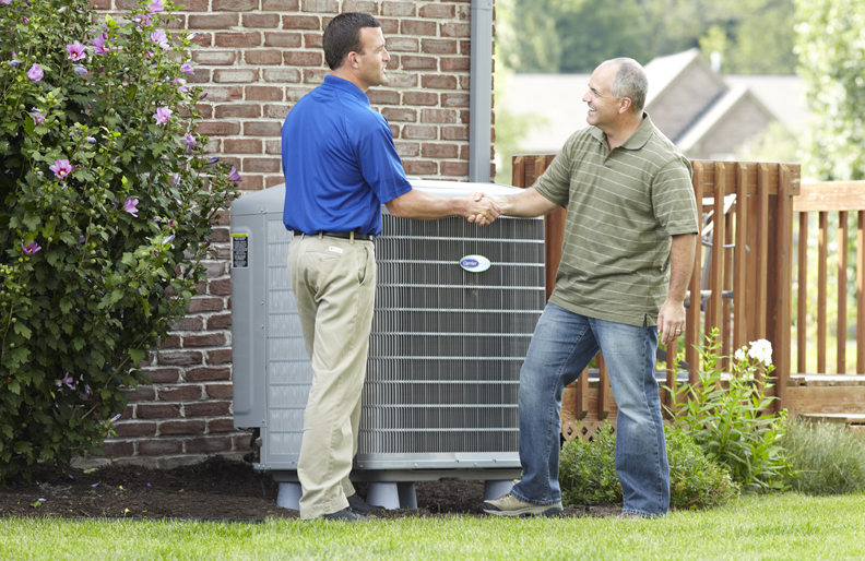 Carrier dealer shaking hands with homeowner near AC unit