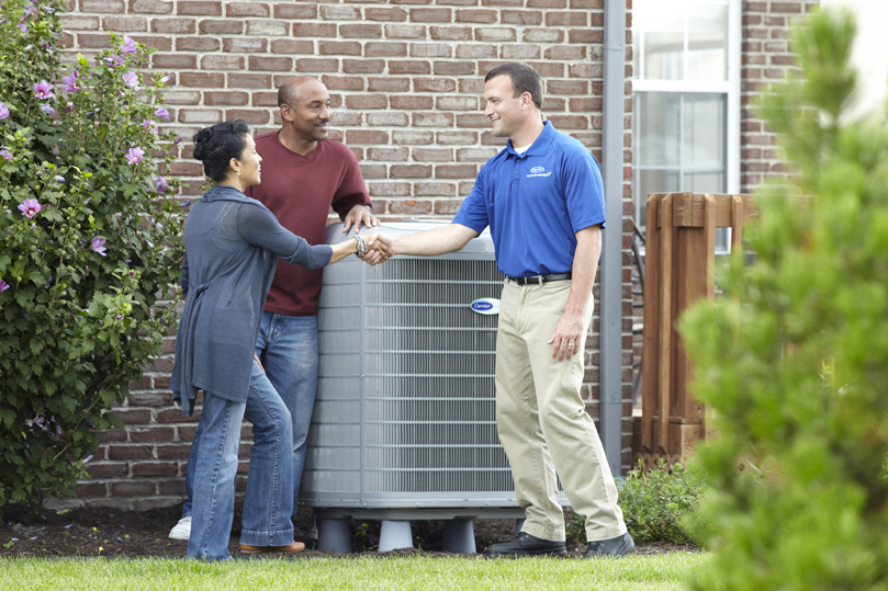 Carrier dealer shaking hands with homeowners outdoors