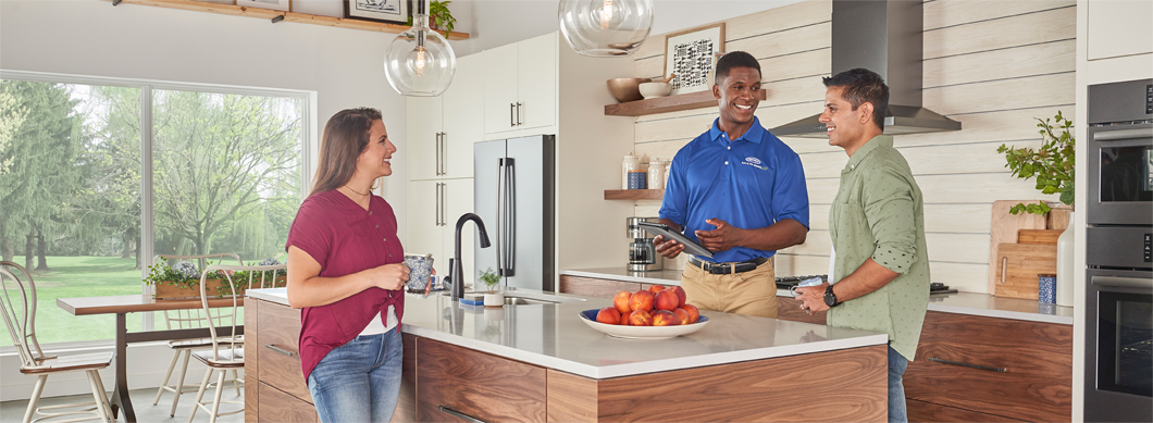 Carrier dealer with homeowners in kitchen